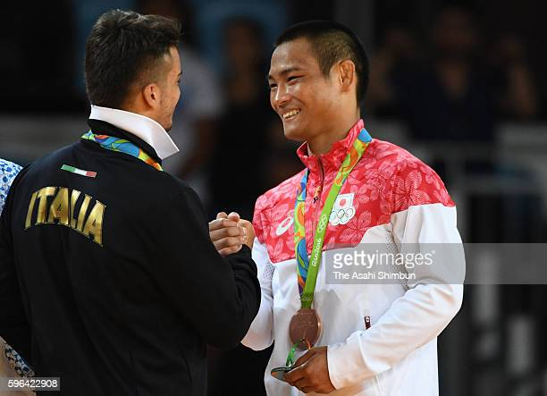 Gold medalist Fabio Basile of Italy and bronze medalist Masashi Ebinuma of Japan shake hands on the podium during the medal ceremony for the Men's...