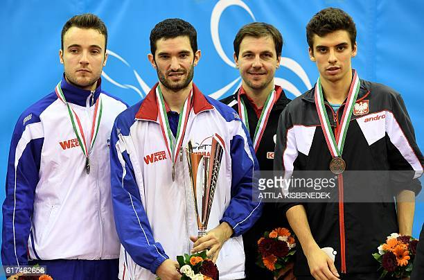 Gold medalist France's Emmanuel Lebesson poses on the podium with silver medalist France's Simon Gauzy bronze medalists Germany's Timo Boll and...