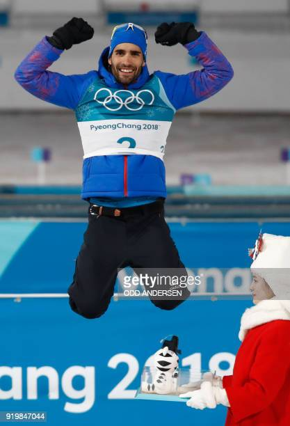 TOPSHOT Gold medalist France's Martin Fourcade celebrates on the podium during the victory ceremony in the men's 15km mass start biathlon event...