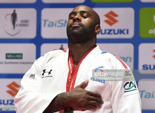 Gold medalist France's Teddy Riner listens to his national anthem as he celebrates on the podium after winning the mens 100kg category at the World...