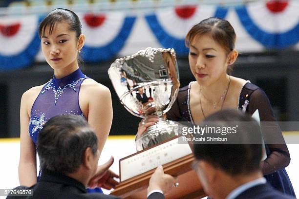 Gold medalist Fumie Suguri receives the trophy while silver medalist Shizuka Arakawa watches at the medal ceremony for the Women's Singles during day...