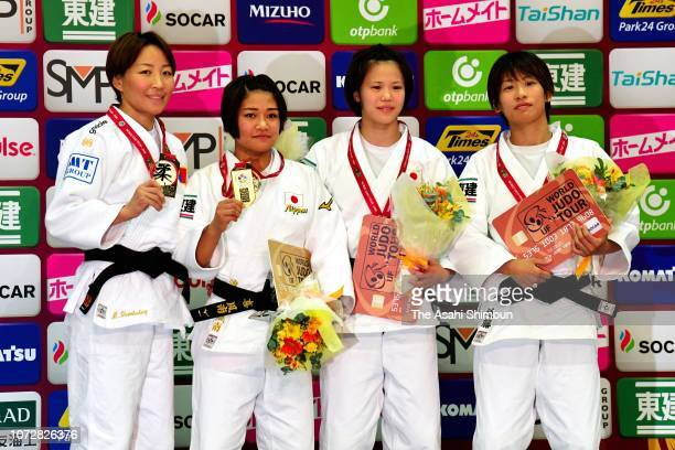 Gold medalist Funa Tonaki of Japan celebrates with silver medalist Urantsetseg Munkhbat of Mongolia and bronze medalists Hiromi Endo of Japan and Ami...