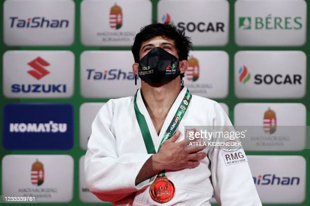 Gold medalist Georgia's Lasha Shavdatuashvili listens to the country's national anthem as he celebrates on the podium after the final of the men's...