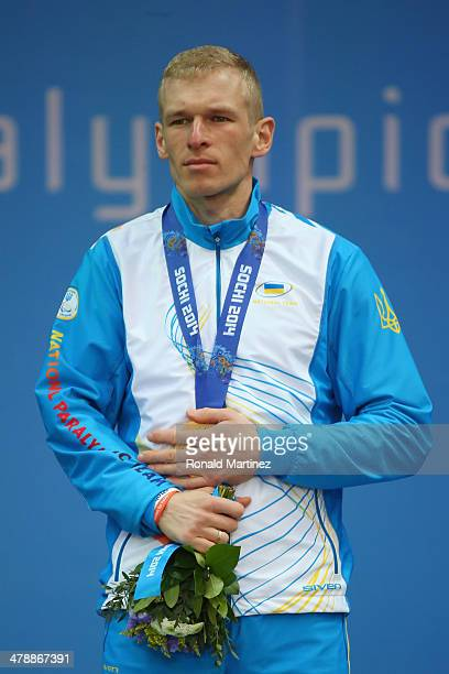 Gold medalist Grygorii Vovchynskyi of Ukraine covers his medal at the medal ceremony for the Men's 15km Standing Biathlon on day eight of the Sochi...