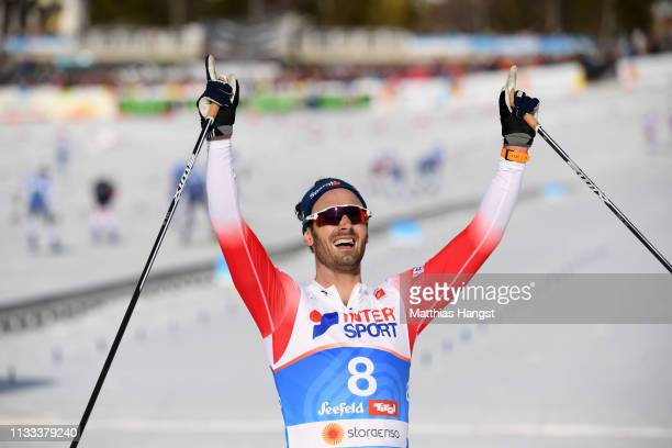 Gold medalist Hans Christer Holund of Norway celebrates as he crosses the finish line to win the Men's Cross Country 50k race during the FIS Nordic...