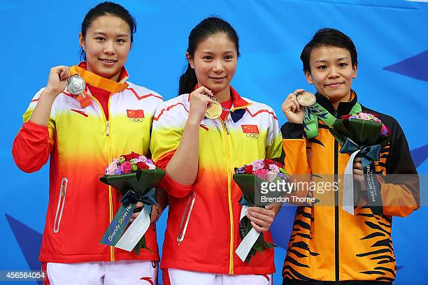 Gold medalist He Zi of China Silver medalist Wang Han of China and Bronze medalist Jun Hoong Cheong of Malaysia pose atop the podium following the...