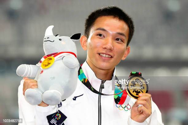 Gold medalist Hiroto Inoue of Japan celebrates on the podium at the medal ceremony for the Men's Marathon at the GBK Main Stadium on day seven of the...