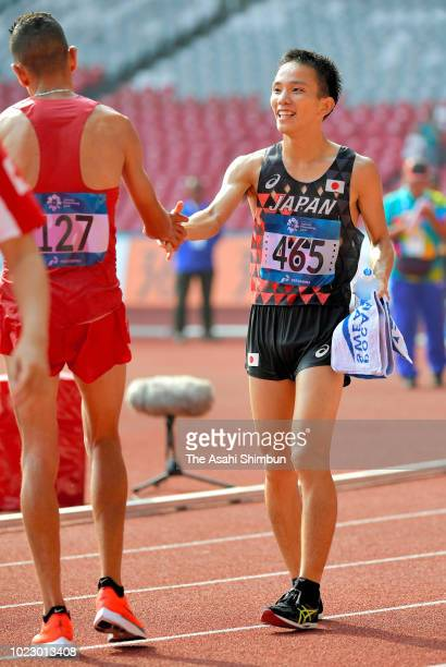 Gold medalist Hiroto Inoue of Japan shakes hands with silver medalist Elhassan Elabbassi of Bahrain after competing in the Men's Marathon at the GBK...