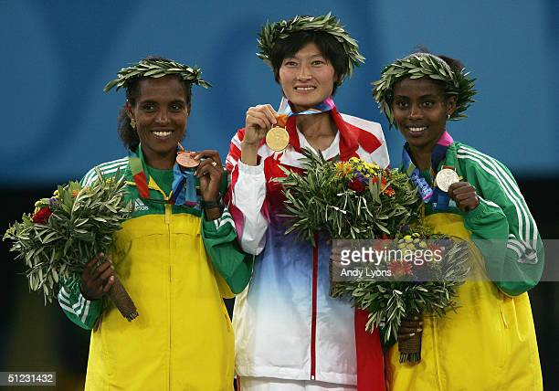 Gold medalist Huina Xing of China silver medalist Ejegayehu Dibaba of Ethiopia and bronze medalist Derartu Tulu of Ethiopia celebrate on the podium...