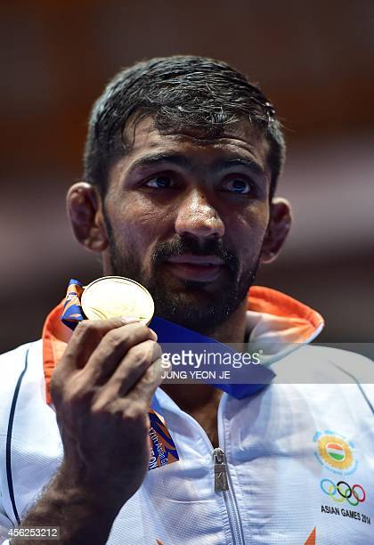 Gold medalist India's Yogeshwar Dutt poses in the medal ceremony of the men's freestyle 65 kg wrestling event during the 2014 Asian Games at the...