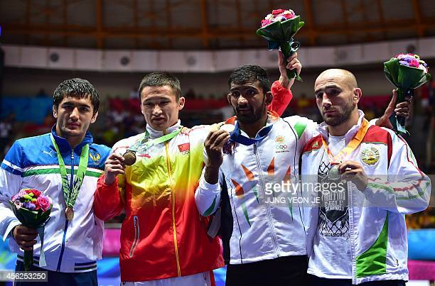 Gold medalist India's Yogeshwar Dutt poses with silver medalist Tajikistan's Zalimkhan Yusupov and bronze medalists China's Yeerlanbieke Katai and...