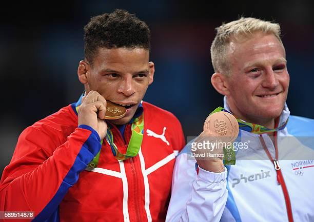 Gold medalist Ismael Borrero Molina of Cuba and bronze medalist StigAndre Berge of Norway celebrate on the podium following the Men's GrecoRoman 59...