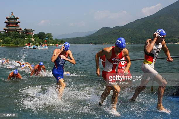 Gold medalist Jan Frodeno of Germany competes with Sven Riederer of Switzerland in the swimming portion of the Men's Triathlon Final at the Triathlon...