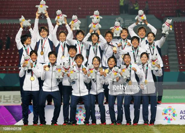 Gold medalist Japan celebrates on the podium at the medal ceremony for the Football Women's event after the Women's Football final between Japan and...