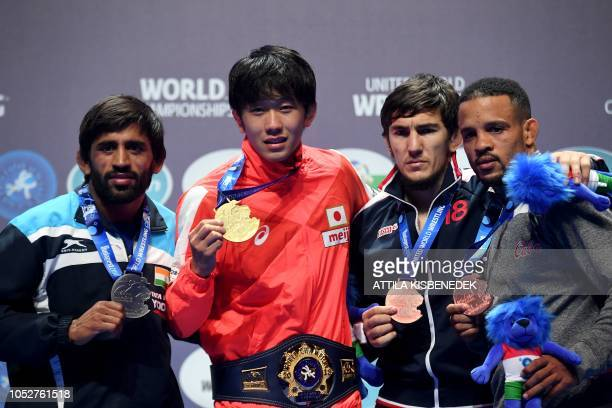Gold medalist Japan's Takuto Otoguru celebrates on the podium beside second placed India's Bajrang Bajrang and bronze medalists Russia's Akhmed...