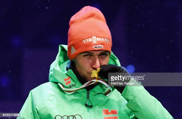 Gold medalist Johannes Rydzek of Germany kisses his medal during the medal ceremony for the Men's Nordic Combined HS100 Ski Jumping/10km CrossCountry...