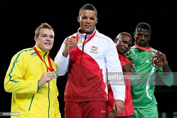Gold medalist Joseph Joyce of England poses with silver medalist Joseph Goodall of Australia and bronze medalists Mike Sekabembe of Uganda and Efe...