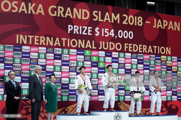 Gold medalist Joshiro Maruyama of Japan stands for the national anthem with silver medalist Hifumi Abe of Japan and bronze medalists Aram Grigoryan...