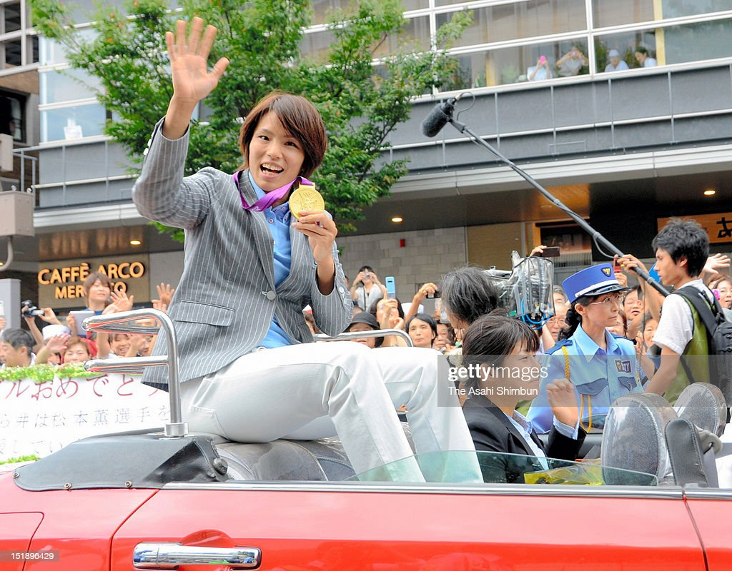 Gold medalist judoka Kaori Matsumoto waves to the crowd showing her Olympic medal, as she makes a victory parade through the streets of her hometown Kanazawa on September 11, 2012 in Kanazawa, Japan. 50,000 people attend to see Matsumoto.