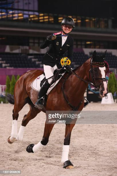 Gold medalist Julia Krajewski of Team Germany riding Amande de B'Neville celebrates with the gold medal after the Eventing Individual Jumping medal...