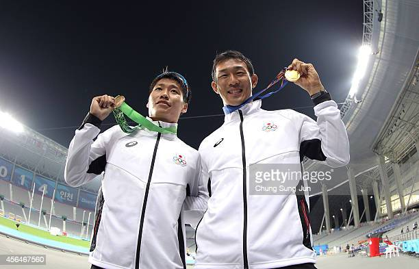 Gold medalist Keisuke Ushiro of Japan and Bronze medalist Akihiro Nakamura of Japan celebrate after winning the Men's Decathlon 1500m Final on day...