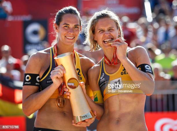 Gold medalist Kira Walkenhorst and Laura Ludwig of Germany lift their winners trophy during the medal ceremony for the Women's Final on August 05,...