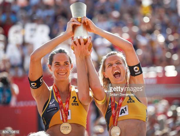 Gold medalist Kira Walkenhorst and Laura Ludwig of Germany lift their winners trophy during the medal ceremony for the Women's Final on August 05...