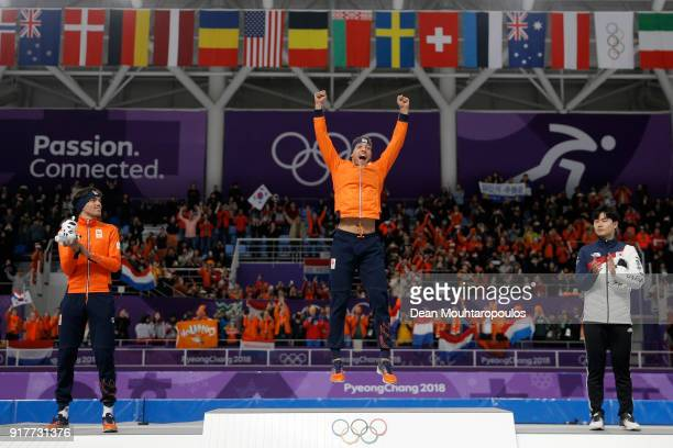 Gold medalist Kjeld Nuis of the Netherlands celebrates with silver medalist Patrick Roest of the Netherlands and bronze medalist Min Seok Kim of...
