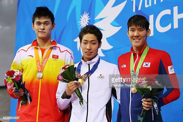 Gold medalist Kosuke Hagino of Japan Silver medalist Sun Yang of China and Bronze medalist Park Taehwan of South Korea pose atop the podium after the...
