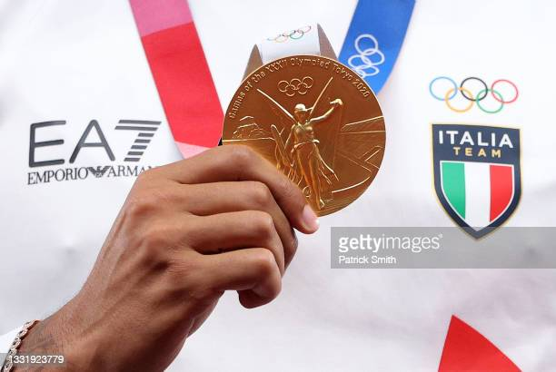 Gold medalist Lamont Marcell Jacobs of Team Italy holds up his gold medal on the podium during the medal ceremony for the Men's 100m on day ten of...