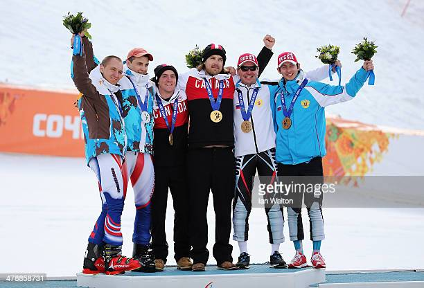 Gold medalist Mac Marcoux of Canada and guide Robin Femy celebrate with silver medalists Jakub Krako of Slovakia and guide Martin Motyka and bronze...