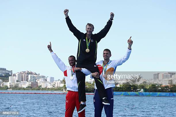 Gold medalist Mahe Drysdale of New Zealand is lifted by Silver medalist Damir Martin of Croatia and bronze medalist Ondrej Synek of the Czech...