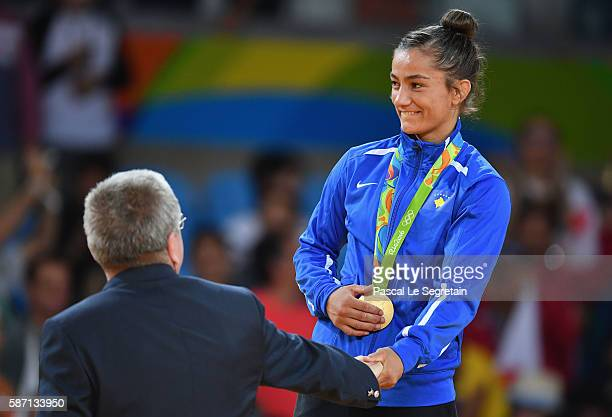 Gold medalist Majlinda Kelmendi of Kosovo is presented her medal by IOC President Thomas Bach during the medal ceremony for the Women's 52kg Judoon...