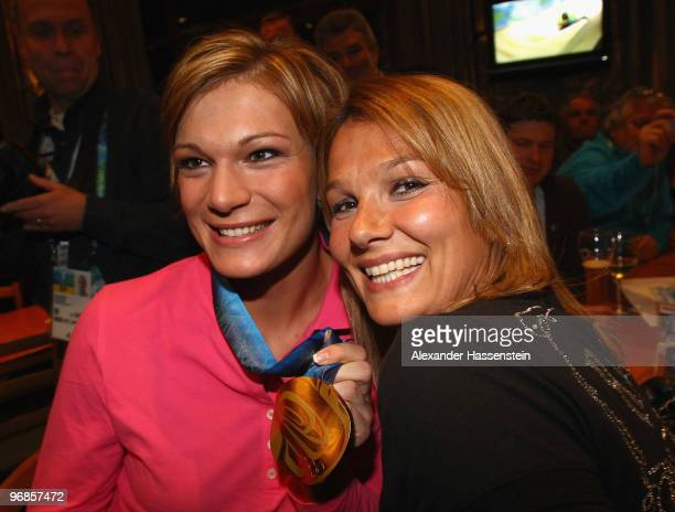Gold medalist Maria Riesch of Germany poses with Olympic gold medalist swimmer Franziska van Almsick and her gold medal for the women's Super...