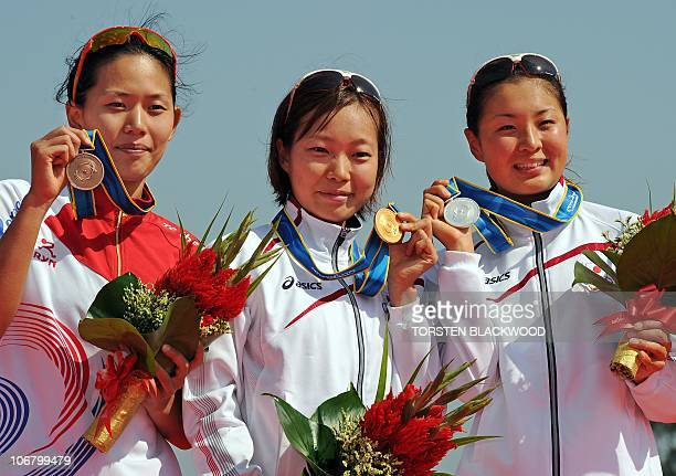 Gold medalist Mariko Adachi of Japan poses on the podium with fellow silver medalist Akane Tsuchihashi and bronze medalist Jang Yun Jung of South...