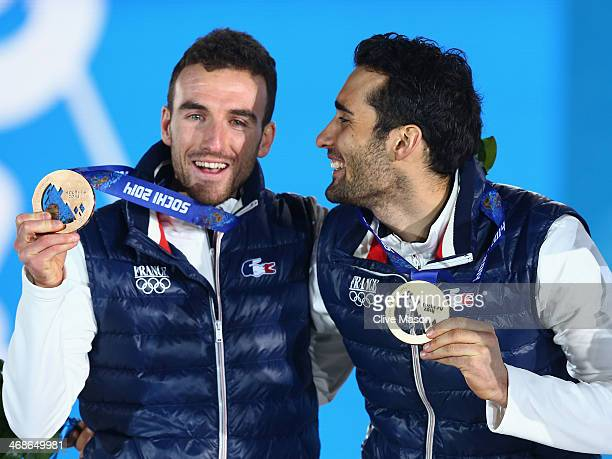 Gold medalist Martin Fourcade of France and bronze medalist Jean Guillaume Beatrix of France celebrate on the podium during the medal ceremony for...