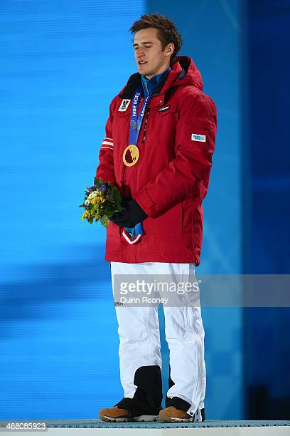 Gold medalist Matthias Mayer of Austria stands on the podium for the national anthem during the medal ceremony for the Alpine Skiing Men's Downhill...