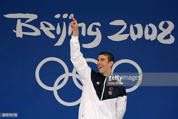Gold medalist Michael Phelps of the United States celebrates on the podium during the medal ceremony for the Men's 100m Butterfly Final held at the...