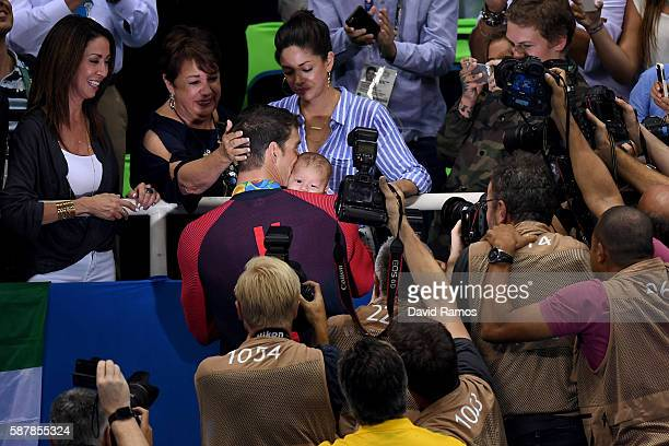 Gold medalist Michael Phelps of the United States celebrates with his mother Deborah Phelps fiancee Nicole Johnson and son Boomer during the medal...