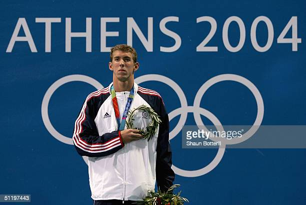 Gold medalist Michael Phelps of the United States listens to the national anthem after receiving his medal for the men's swimming 100 metre butterfly...