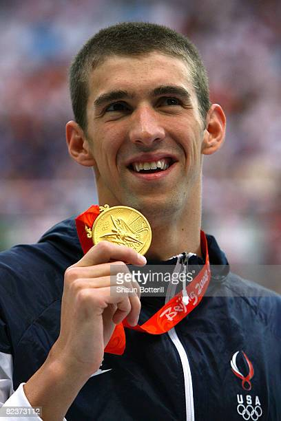 Gold medalist Michael Phelps of the United States poses during the medal ceremony for the Men's 100m Butterfly Final held at the National Aquatics...