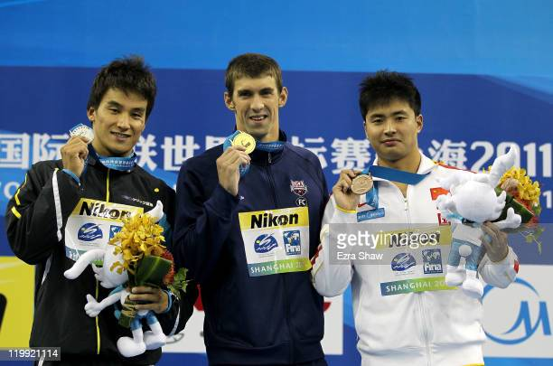 Gold medalist Michael Phelps of the United States poses with silver medalist Takeshi Matsuda of Japan and bronze medalist Peng Wu of China after the...