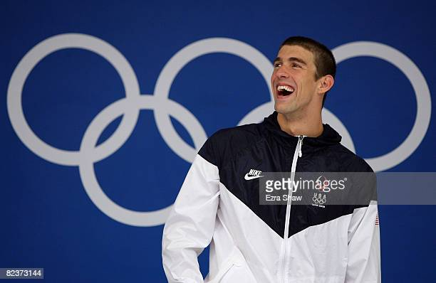 Gold medalist Michael Phelps of the United States smiles as he stands on the podium during the medal ceremony for the Men's 100m Butterfly Final held...