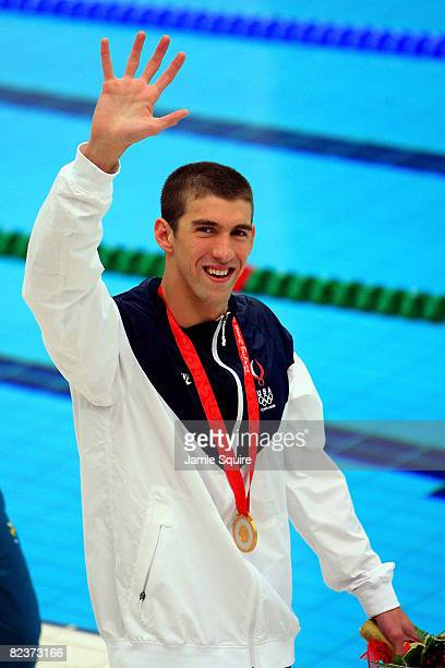 Gold medalist Michael Phelps of the United States waves during the medal ceremony for the Men's 100m Butterfly Final held at the National Aquatics...