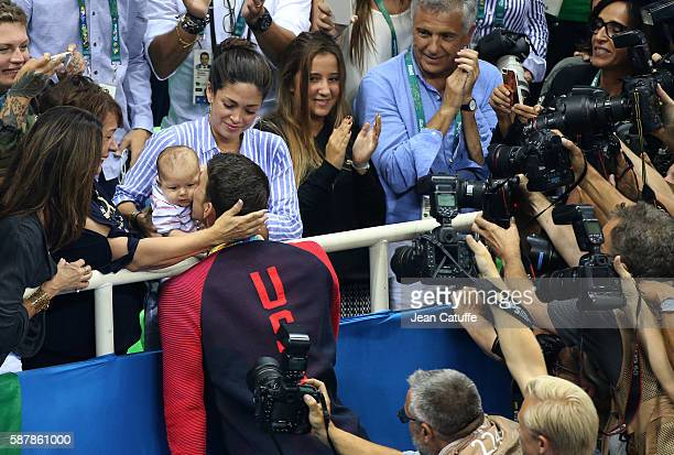 Gold medalist Michael Phelps of USA is congratulated by his fiancee Nicole Johnson their 3 months old baby Boomer Phelps and his mother Debbie Phelps...