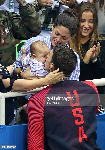 Gold medalist Michael Phelps of USA kisses his 3 months old son Boomer Phelps while his fiancee Nicole Johnson looks on following the medal ceremony...