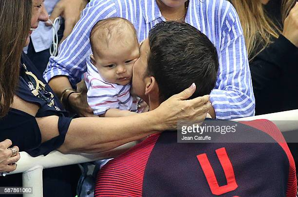 Gold medalist Michael Phelps of USA kisses his 3 months old son Boomer Phelps following the medal ceremony for the men's 200m butterfly on day 4 of...