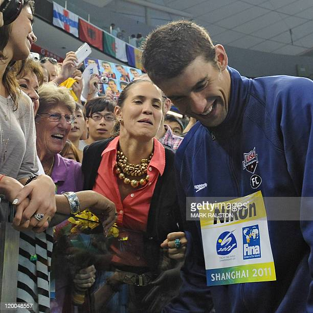 US gold medalist Michael Phelps smiles after he talked to relatives and friends during the award ceremony for the final of the men's 4x200metre...