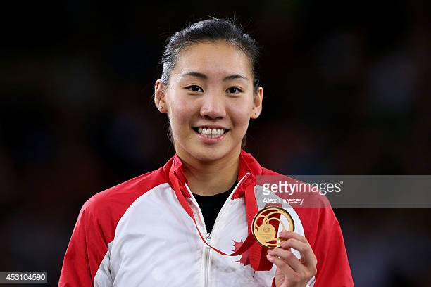 Gold medalist Michelle Li of Canada poses in the medal ceremony for the Women's Singles Gold Medal Match at Emirates Arena during day eleven of the...