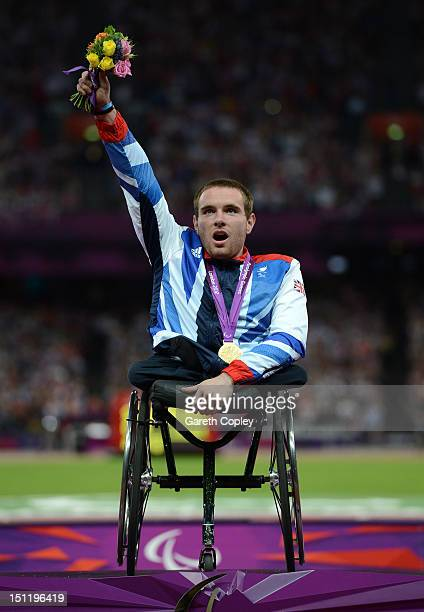 Gold medalist Mickey Bushell of Great Britain poses on the podium during the medal ceremony for the Men's 100m T53 Final on day 5 of the London 2012...